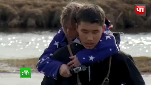 Иркутские подростки носят малышей в школу через реку на плечах